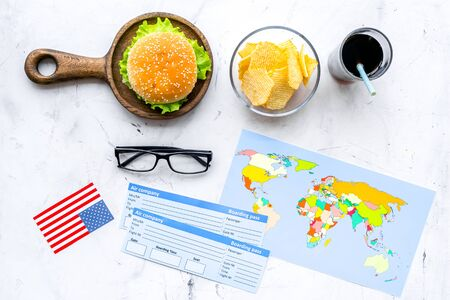 Photo for Traditional food. Burger, chips, map, tickets and USA flag for gastronomical tourism to America on marble background top view - Royalty Free Image