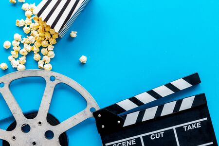 Photo for Watch film in cinema with popcorn, video tape and clapperboard on blue background top view - Royalty Free Image