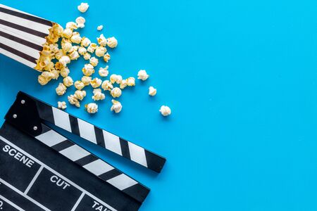 Photo for Go to the cinema with popcorn and clapperboard on blue background top view mock up - Royalty Free Image