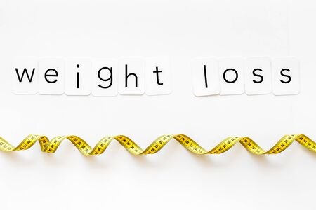 Foto de Diet, fitness and body shape. Weight loss text with measuring tape on white background top view - Imagen libre de derechos