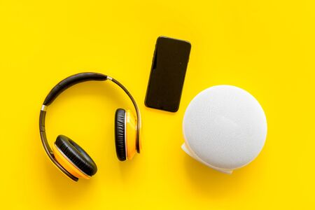 Photo for portable wireless speakers, phone and headphones for music listening on yellow background top view - Royalty Free Image
