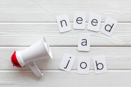 Photo pour Need a job text for announcement and megaphone on white wooden background top view - image libre de droit