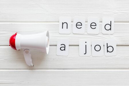 Photo pour Need a job announcement symbol with megaphone and text on white wooden background top view - image libre de droit