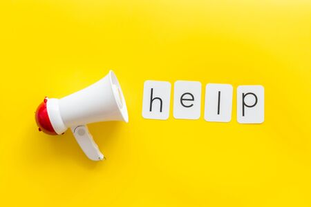 Photo pour Announcement for a help with megaphone and text on yellow background top view - image libre de droit