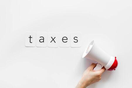 Photo pour Taxes announcement with megaphone and text on white background top view - image libre de droit