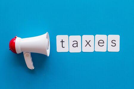 Photo pour Taxes announcement with megaphone and text on blue background top view - image libre de droit
