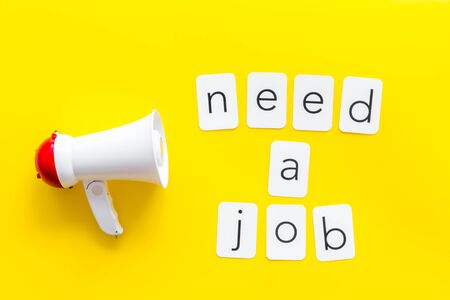 Photo pour Need a job text for announcement and megaphone on yellow background top view - image libre de droit