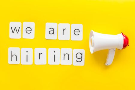Photo pour We are hiring announcement with megaphone and text on yellow background top view. - image libre de droit