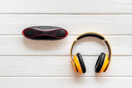 Photo for Portable wireless speakers and headphones as gadgets for listen to the music on white wooden background top view - Royalty Free Image