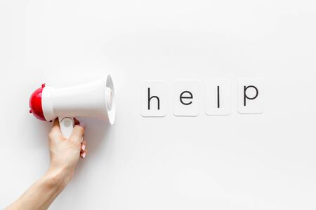 Photo pour Looking for a help concept with text and megaphone on white background top view - image libre de droit
