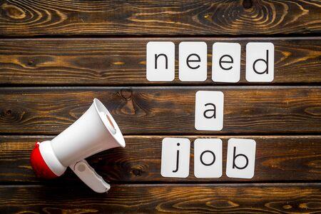 Photo pour Need a job announcement symbol with megaphone and text on wooden background top view - image libre de droit