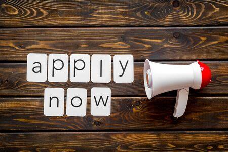 Photo pour loudspeaker and apply now text for announcement on wooden background top view - image libre de droit