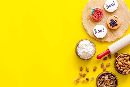 Foto de spooky halloween figures with rolling pin, flour, sugar, almond for cooking treat on yellow background top view mock up - Imagen libre de derechos