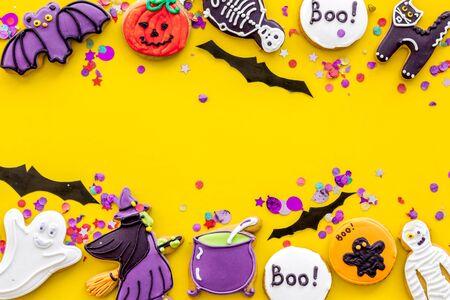 Foto de Creepy cookies for halloween treat frame on yellow background top view mockup - Imagen libre de derechos