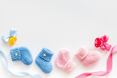 Foto de Blue and pink knitted footwear with dummy for baby boy and girl on white background top view mock up - Imagen libre de derechos