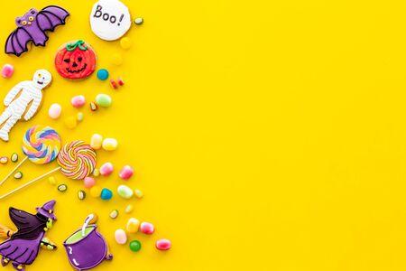 Foto de Celebration halloween and party decorations. Creepy cookies for halloween treat frame on yellow background top view mockup - Imagen libre de derechos