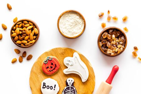Foto de Celebration halloween and party decorations. Cooking creepy cookies concept with almonds, pin, flour on white background top view - Imagen libre de derechos