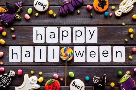 Foto de Halloween cookies frame in shape of spooky figures with happy halloween copy on wooden background top view - Imagen libre de derechos