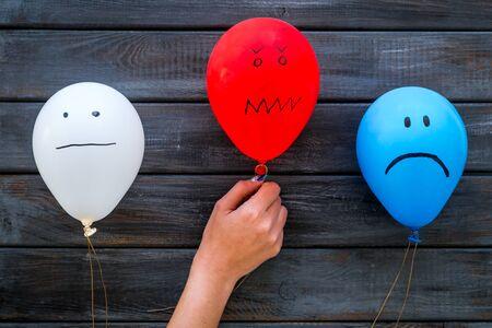 Foto de Negative emotions concept. Balloons with drawn faces on dark wooden background top view. - Imagen libre de derechos