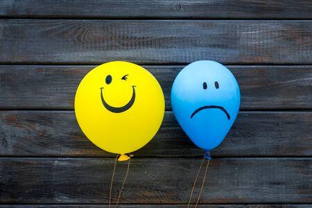 Foto de Treat depression concept. Balloons with sad and smiling faces on dark wooden background top view - Imagen libre de derechos