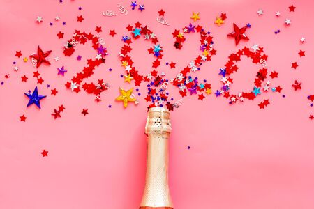 Photo pour Celebrate New Year 2020. Date on confetti near champagne bottle on pink background top view. - image libre de droit