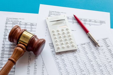 Foto de Taxes debt concept. Judge hammer near financial documents on blue background. - Imagen libre de derechos