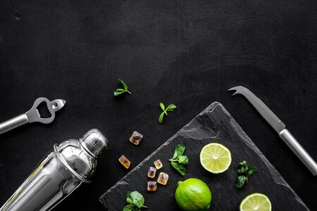 Photo pour Bartender work desk with equipment and cocktail ingredietns Shaker, lime, ice on black background top-down frame copy space - image libre de droit
