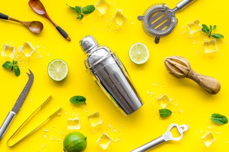 Photo pour Bartender work desk with equipment and cocktail ingredietns Shaker, lime, ice on yellow background top-down. - image libre de droit