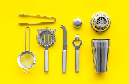 Photo pour Bartender equipment set with shaker and stainer on yellow background top-down pattern. - image libre de droit