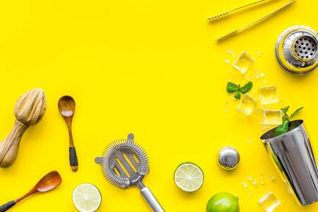 Photo pour Bar background. Tools and ingredients for making cocktails. Shaker, lime, ice on yellow background top-down. - image libre de droit