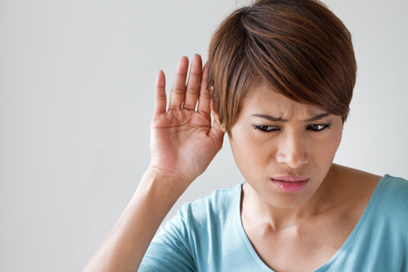 Foto de woman suffers from hearing impairment, hard of hearing, hearing loss, acoustic or ear problem, deafness with text space - Imagen libre de derechos