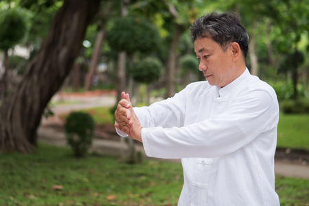 Photo pour old man practicing kungfu or tai chi in the park, healthy lifestyle meditation exercise concept - image libre de droit