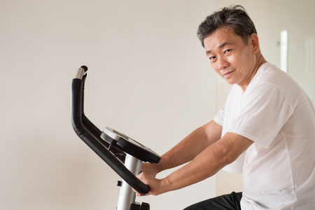 Photo pour old senior man cycling, exercising, working out in gym with modern cycling machine - image libre de droit
