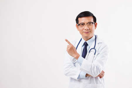 Foto de male doctor pointing finger up away to the left side - Imagen libre de derechos