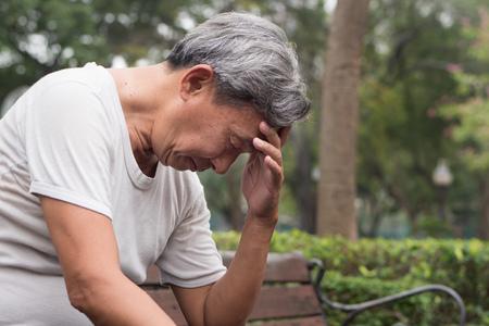 Foto de sad hopeless frustrated old retired senior man sitting in public park, urban poverty concept - Imagen libre de derechos