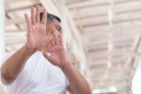 Foto de old man showing rejecting, stopping hand gesture; concept of forbidding, no way, rejection, negative answer, halt, stop, warning, social distancing; southeast asian senior old man model - Imagen libre de derechos