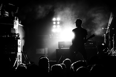 Photo pour silhouette of guitar player in action on concert stage, black and white - image libre de droit