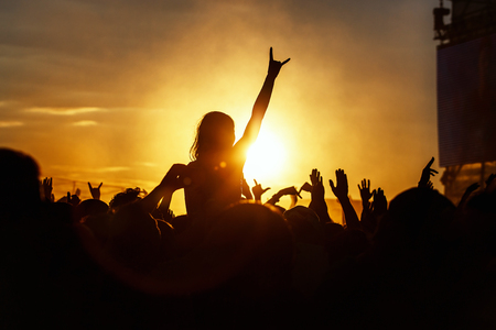 Photo for Young girl enjoys a rock concert, Silhouette on sunset, hands up on openair - Royalty Free Image