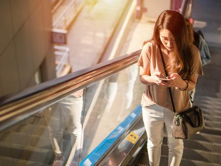 Foto de Young asian woman standing escalator and smiling, Using smartphone searching for social media in the city. - Imagen libre de derechos