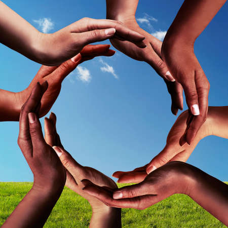 Foto de Conceptual peace and unity symbol of different black african ethnicity hands making a circle together on blue sky and green grass background - Imagen libre de derechos