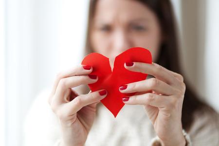 Foto de woman tearing paper heart apart, shallow depth of field - Imagen libre de derechos