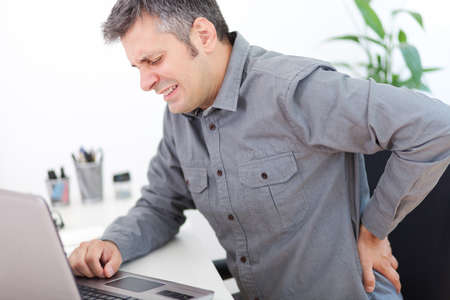 Photo pour Image of a young man having a back pain while sitting at the working desk - image libre de droit