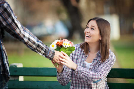 Young woman receiving a bunch of wild flowers on a date