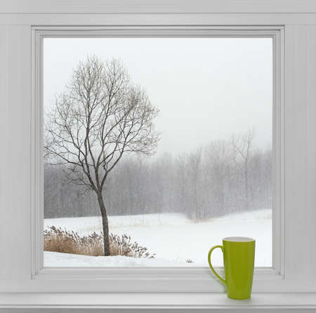 Foto de Green teacup on a windowsill, with winter landscape seen through the window  - Imagen libre de derechos