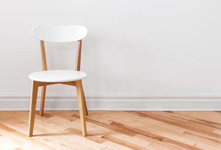Foto de Elegant white chair in an empty room with wooden floor. - Imagen libre de derechos