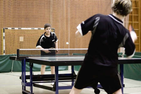 Two persons playing table tennis. Focus on the net of the table.