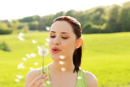 Foto de Woman blowing on a dandelion. - Imagen libre de derechos