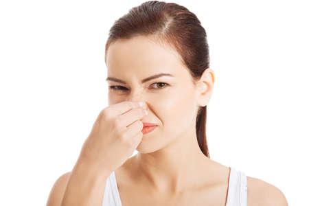 Foto de Portrait of a young woman holding her nose because of a bad smell. - Imagen libre de derechos