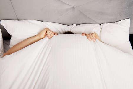 Photo pour Funny man hiding in bed under the sheets. - image libre de droit