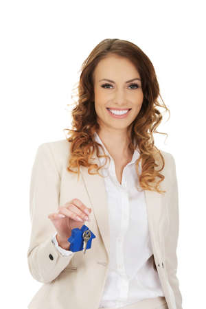 Photo pour Businesswoman real estate agent giving keys. - image libre de droit